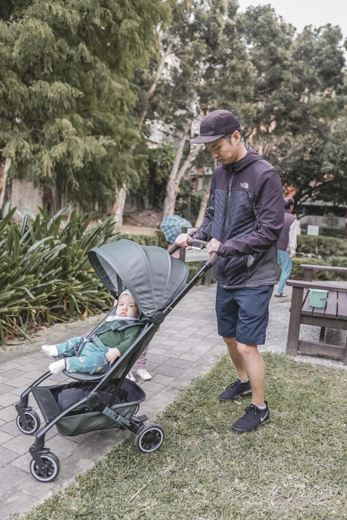A person pushing a stroller with a baby in it  Description automatically generated with medium confidence